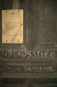 Luftschutzmerkblatt und Kreidebeschriftung an einer Kellertür