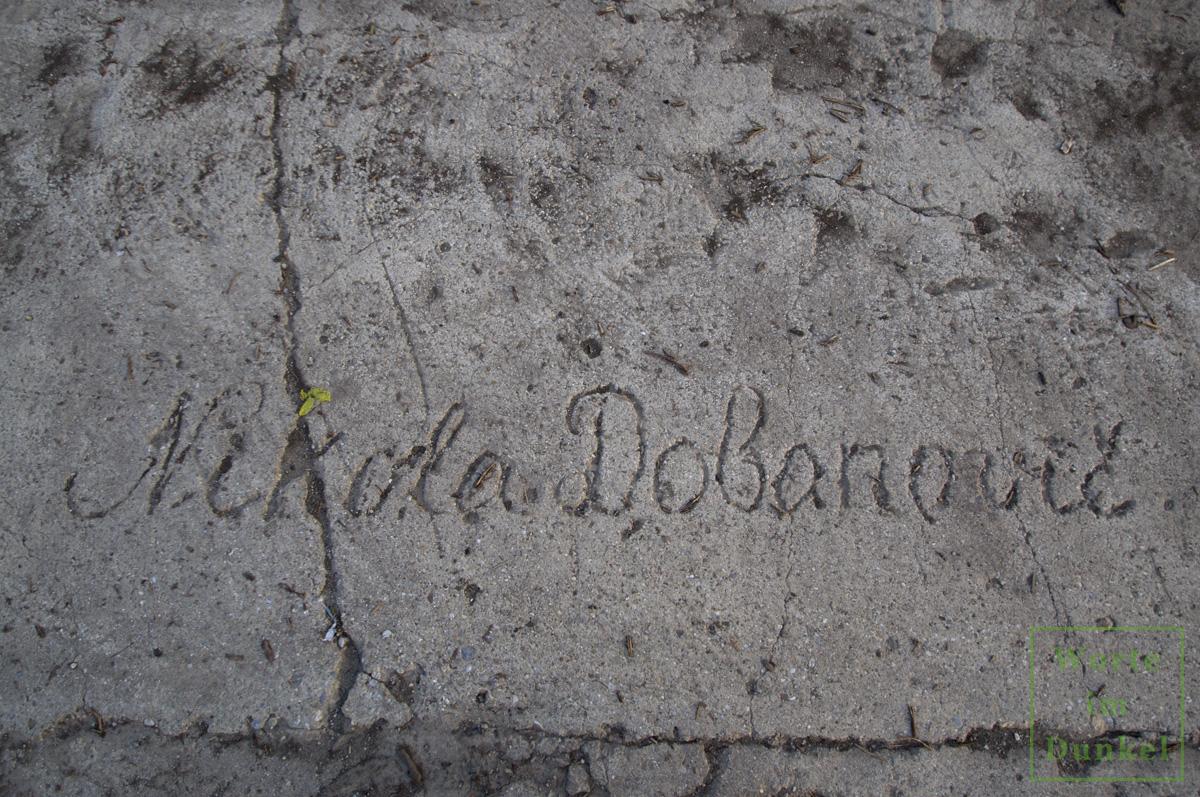 Der Name des serbischen Zwangsarbeiters Nikola Dobanovic, im nassen Beton einer Startbahn verewigt