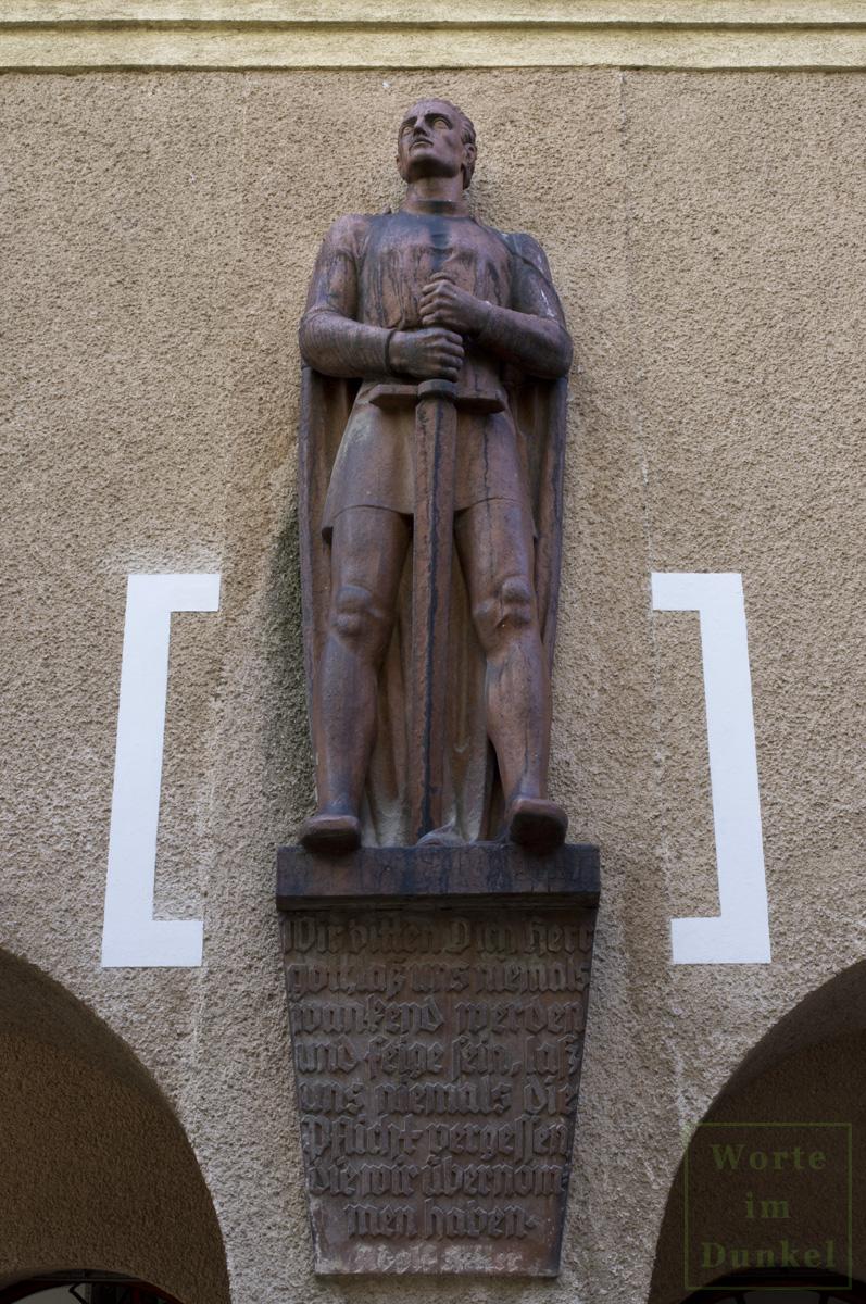 Terrakotta-Figur in Gestalt eines schwerttragenden Kriegers an der Fassade des Thuryhofs – darunter ein Spruch von Adolf Hitler.