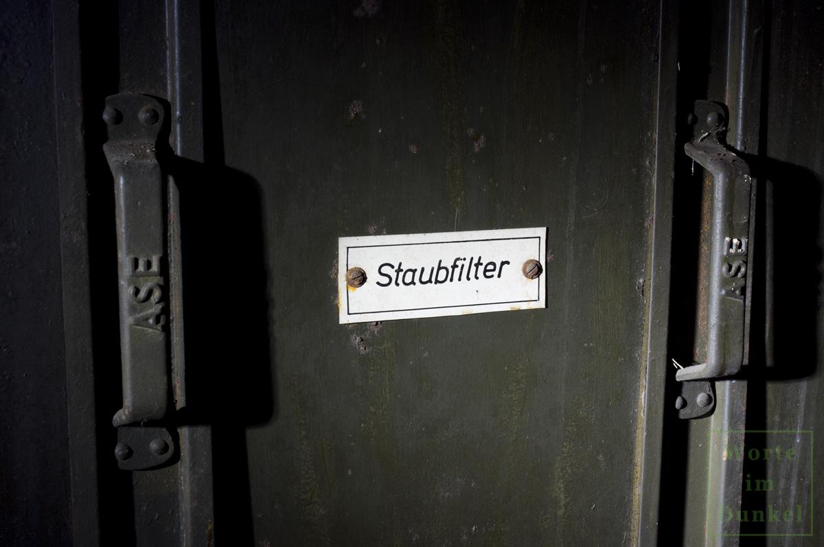 """Plakette """"Staubfilter"""", auf den Handgriffen, die dem Ein- und Ausziehen der Filter dienen, steht der Begriff """"ASE"""", möglicherweise der Hersteller der Staubfilter"""