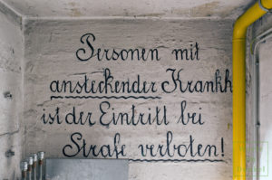 """Aufschrift über dem Abgang in einen Bunker: """"Personen mit ansteckender Krankheit ist der Eintritt bei Strafe verboten!"""""""