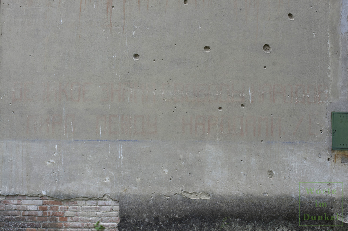 Mauer mit Spuren des Krieges und den verblassten kyrillischen Schriftzeichen aus Stalins Rede vom 9. Mai 1945