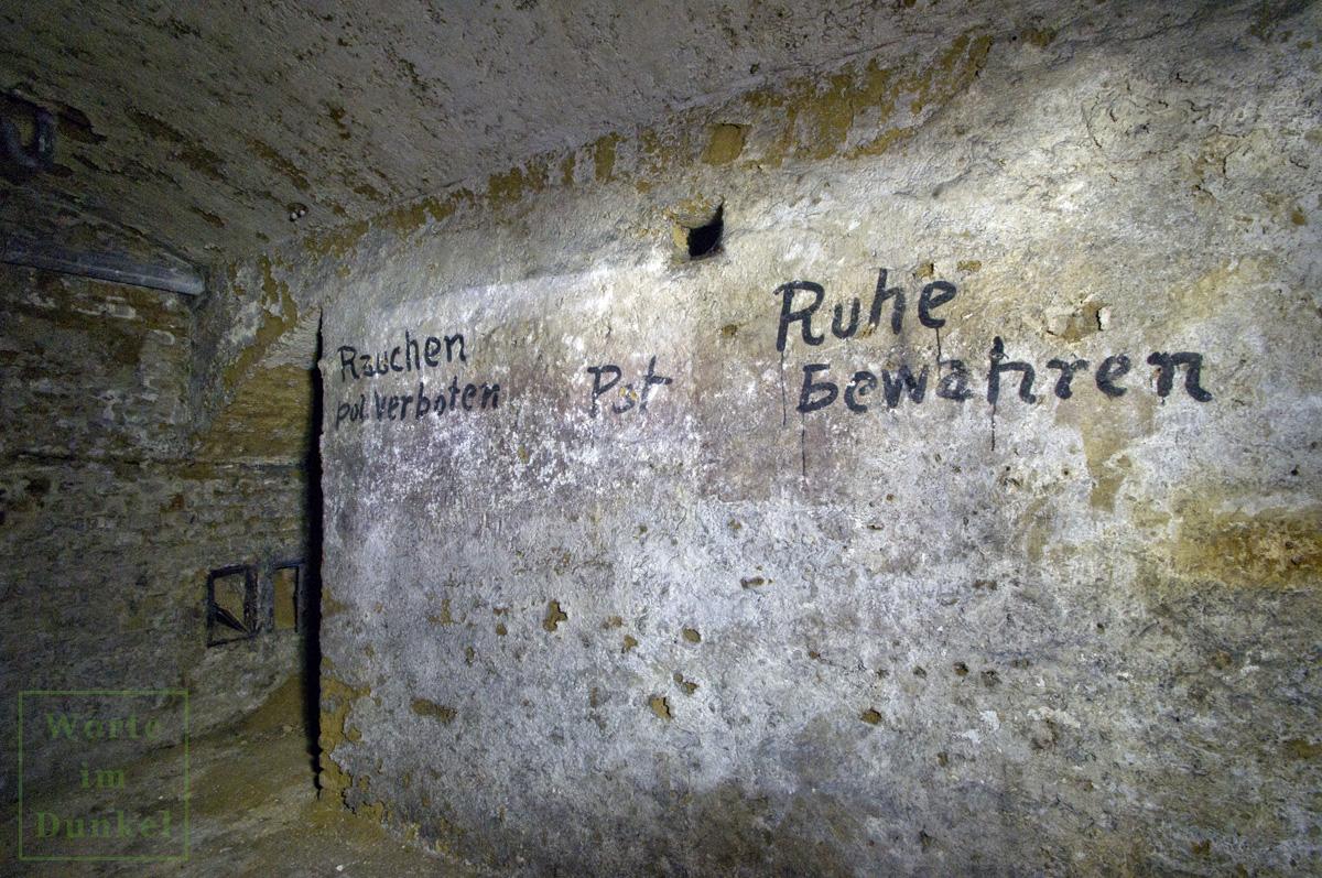 """Die Verhaltenshinweise """"Nicht Rauchen"""", """"Pst"""" und """"Ruhe bewahren"""" an der Mauer eines Wiener Luftschutzkellers"""