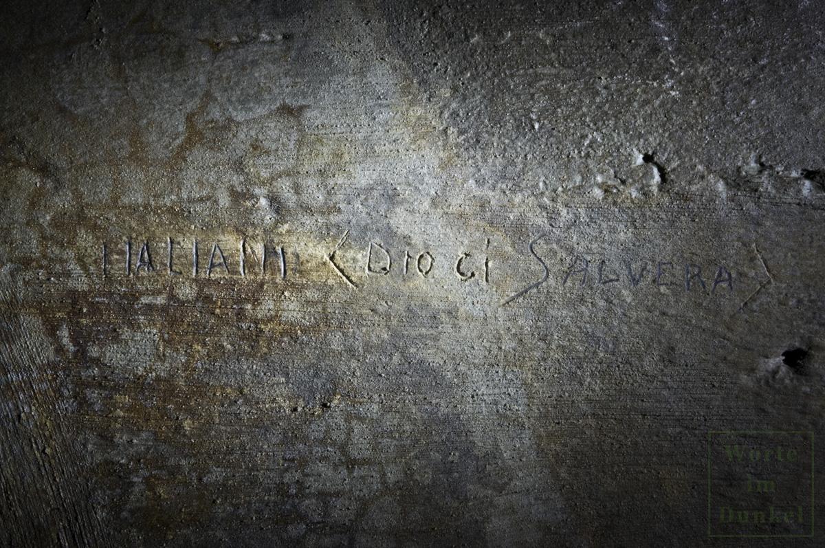 """""""Italiani Dio ci salvera"""", auf deutsch """"Italiener Gott wird uns retten"""" eingeritzt im Beton einer Luftschutzanlage"""