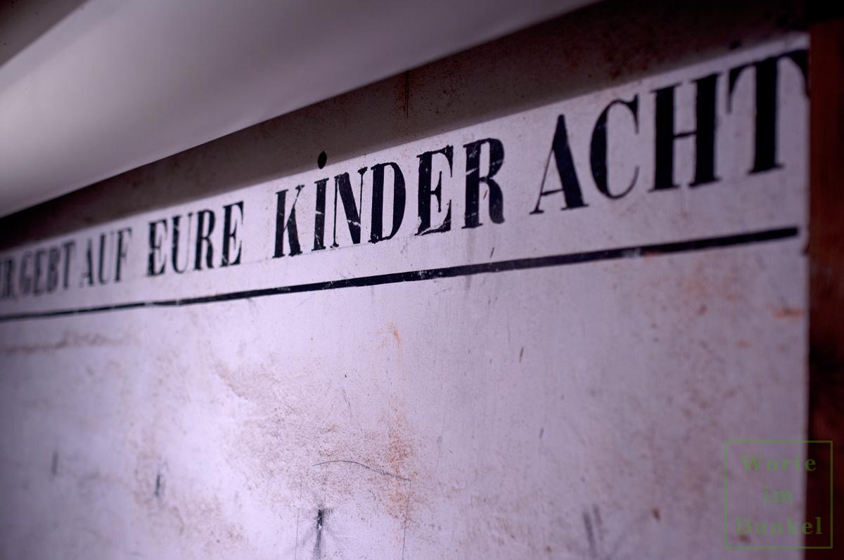 """Aufschrift """"Mütter, gebt auf eure Kinder acht"""" in einem Luftschutzbunker"""