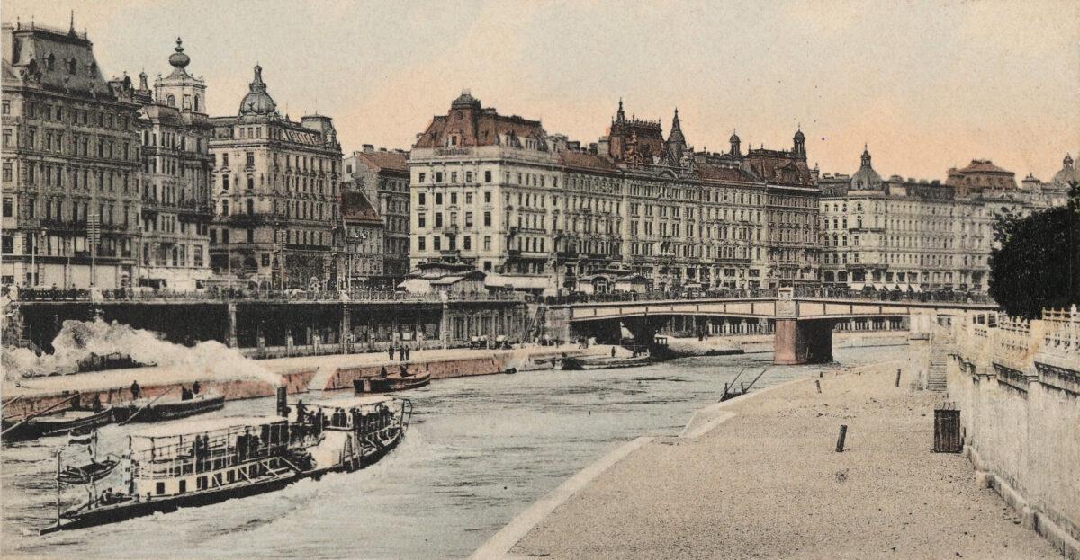 In der Mitte der Ansichtskarte ist die Häuserzeile am Franz-Josefs-Kai zu sehen, die mit der dahinterliegenden die Adlergasse bildete.