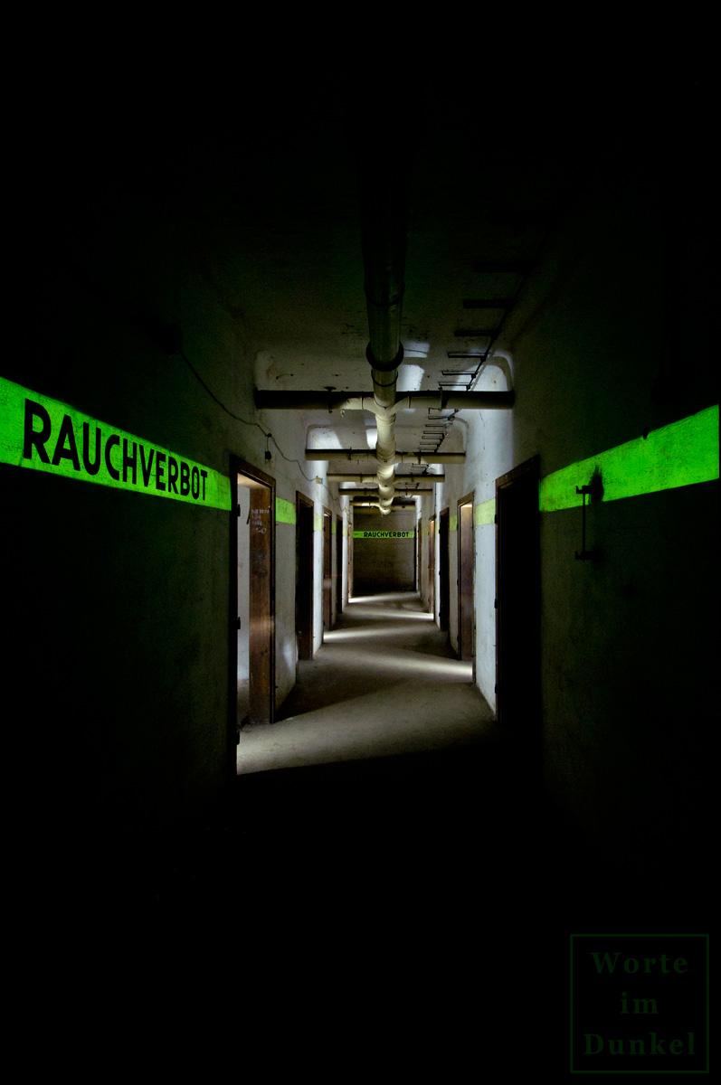 Blick in den Gang eines Luftschutzbunkers. In den Leuchtstreifen wurden wichtige Informationen kundgetan.