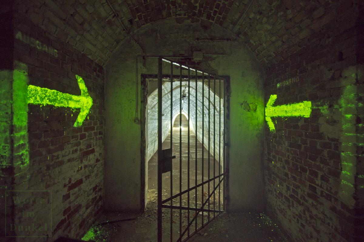 Auch Luftschutzstollen waren mit Leuchthinweisen versehen, hier zwei Pfeile, die in Richtungs des Ausgangs weisen.