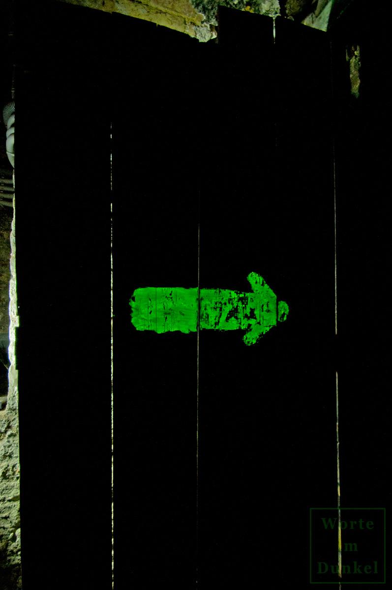 Kleiner Pfeil an einer Kellertür, der entweder in Richtung des Notausstiegs oder des Schutzraumes wies.