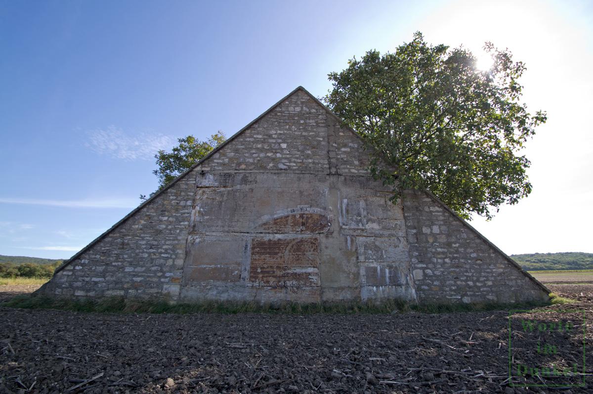 Dieser Bunker wurde mit einer dreieckigen Scheinfassade ausgestattet und diese sogar mit einem aufgemalten Tor und der Jahreszahl HT 1942 versehen.