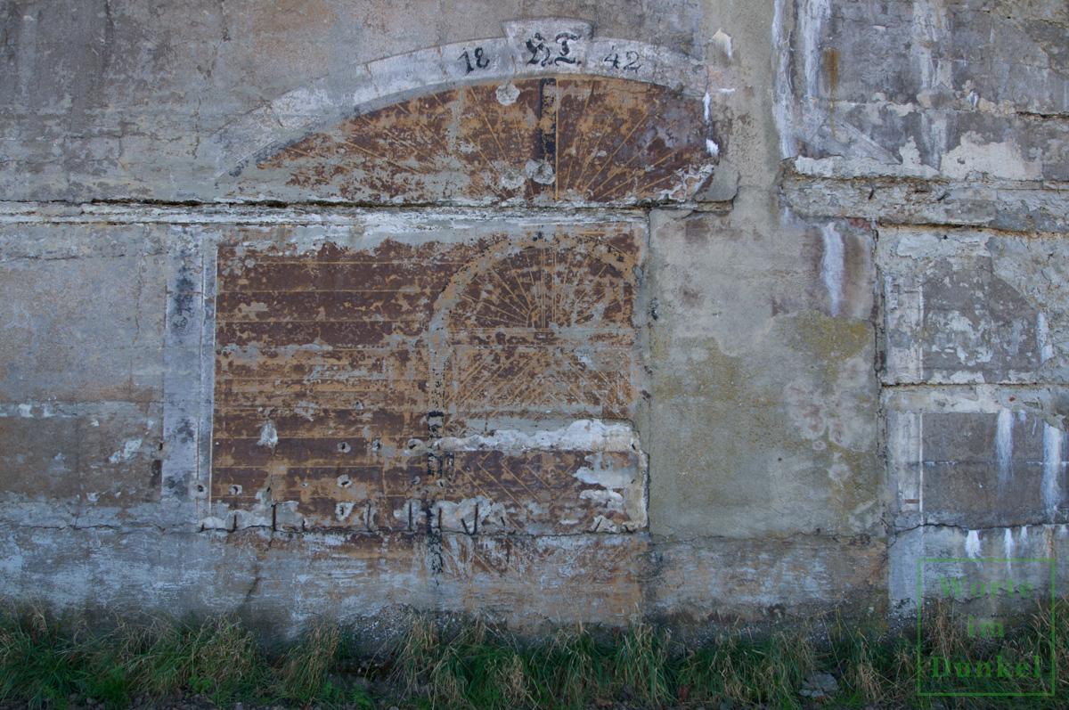 Dieser Bunker wurde mit einer dreieckigen Scheinfassade ausgestattet und diese sogar mit einem aufgemalten Tor und der Jahreszahl HT 1942 versehen – Detail.